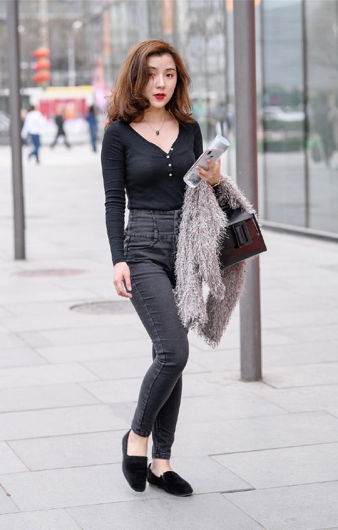 小姐姐街拍V领黑色上衣搭配收腰牛仔紧身裤,展现凹凸身材