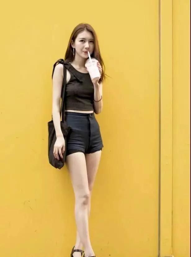 街拍:喝奶茶的小姐姐,黑色吊帶搭配黑色短褲,大長腿很吸睛