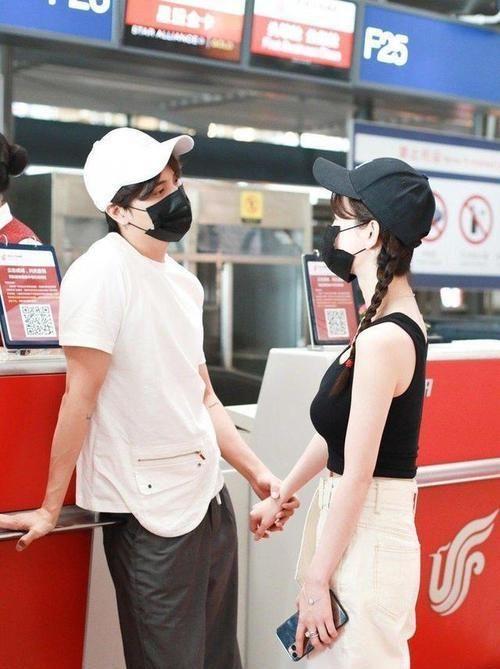 张檬机场私服穿搭,黑色吊带背心搭配一条米白色阔腿裤,休闲随性